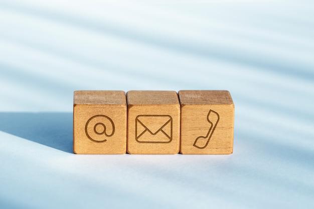 Neem contact met ons concept. houten dobbelstenen met e-mail, mail en telefoonpictogram