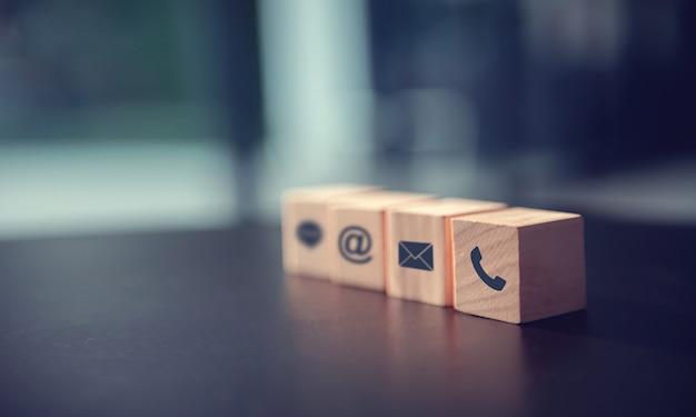 Neem contact met ons op concept, houtblok symbool telefoon, mail en adres op het bureau.