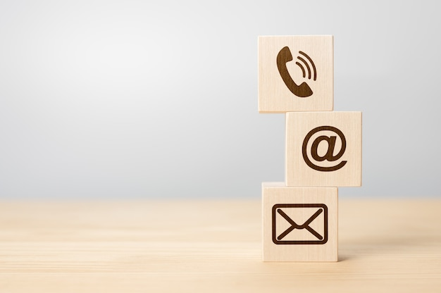 Neem contact met ons op concept, houtblok symbool telefoon, post en adres op bureau. close-up van verschillende contactopties op houten kubussen. houtblok symbool telefoon, post en adres op bureau. kopieer ruimte