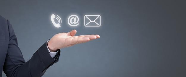 Neem contact met ons op. hand zakenman houdt telefoon-, e-mail- en postpictogrammen vast. hotline voor klantenondersteuning