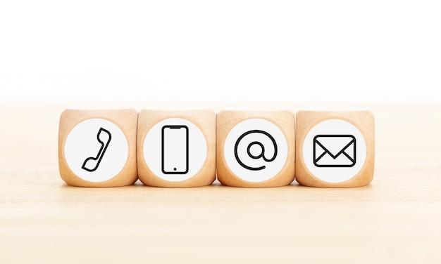 Neem contact met ons op pictogrammen in houten blokken op houten bureau. kopieer ruimte.
