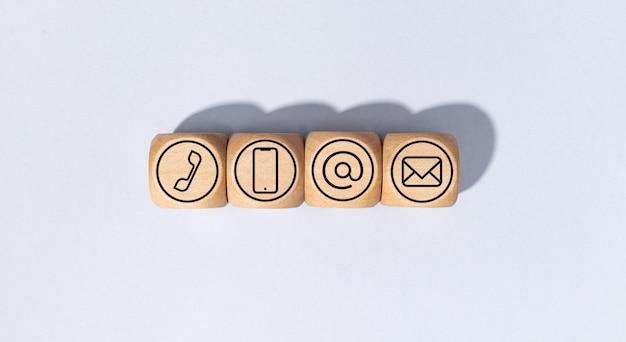 Neem contact met ons op pictogrammen op houten blokken geïsoleerd op een grijze achtergrond