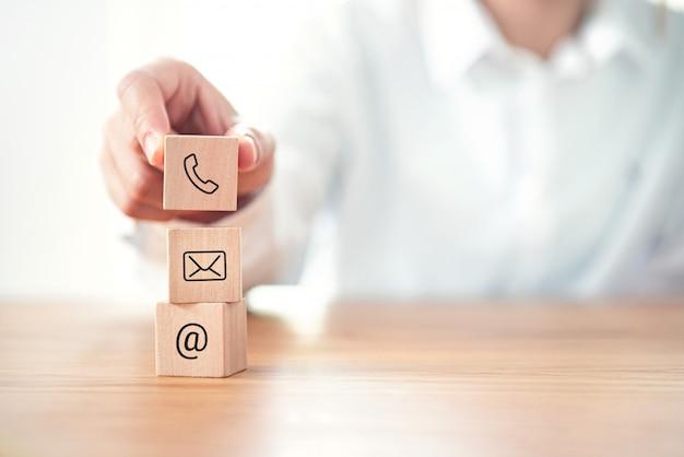 Neem contact met ons op, zakenman hand met (mail, telefoon, e-mail) pictogram