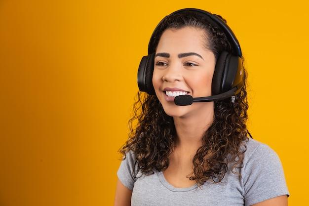 Neem contact op met de callcenterservice. klantenondersteuning, vrouwelijke verkoopagent. beller of operator van telefoniste of zakenvrouw in headset. afro jonge vrouw. zoomconferentie. gele achtergrond