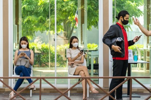 Neem de temperatuur voor de klant met gezichtsmasker voordat u het restaurant binnengaat