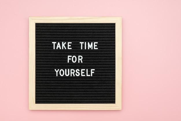 Neem de tijd voor jezelf. motiverende citaat op letterboard op roze achtergrond. bovenaanzicht plat lag kopieer ruimte