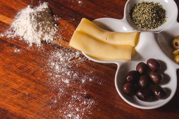 Neem detail van ingrediënten voor een pizza op een houten tafel.