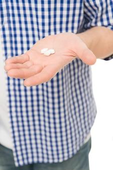 Neem deze pil. pillen en medicijnen. geneeskundepil of vitamine op mannenhand. witte vitaminepillen. vitamine-complex. vitamine suppletie. gezondheidszorg voor een betere gezondheid. gezondheidshulp. een goede gezondheid inspireren.