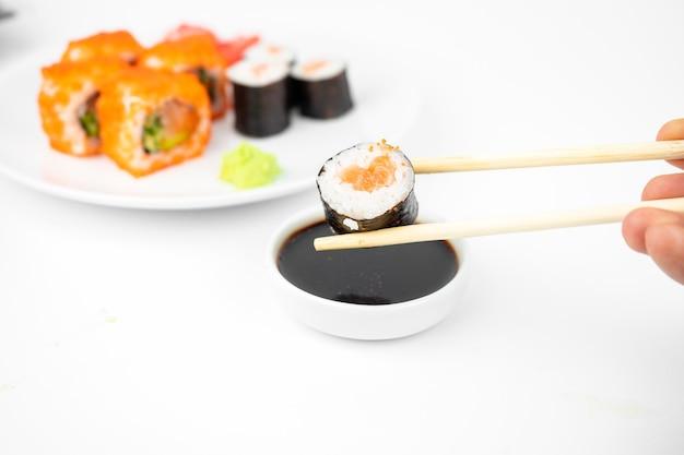 Neem een california maki-rolletjes met bamboe-eetstokjes en doe deze in sojasaus. roze gember, wasabi. aziatisch eten, japanse keuken achtergrond