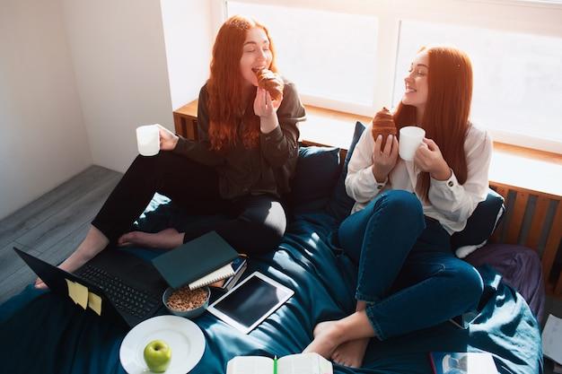 Neem een pauze, eet tussen de lessen door. twee roodharige studenten studeren thuis of in een studentenflat. ze bereiden zich voor op examens.
