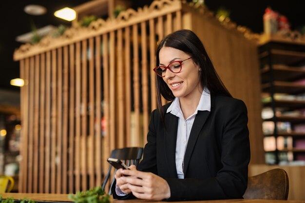 Neem een pauze. jonge moderne bedrijfsvrouw die een onderbreking van het werk in een koffiewinkel neemt. telefoon gebruiken met een glimlach op haar gezicht.