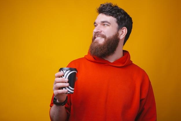 Neem je koffie mee. de foto van de gebaarde kerel houdt een document om koffiekop op gele ruimte te gaan.