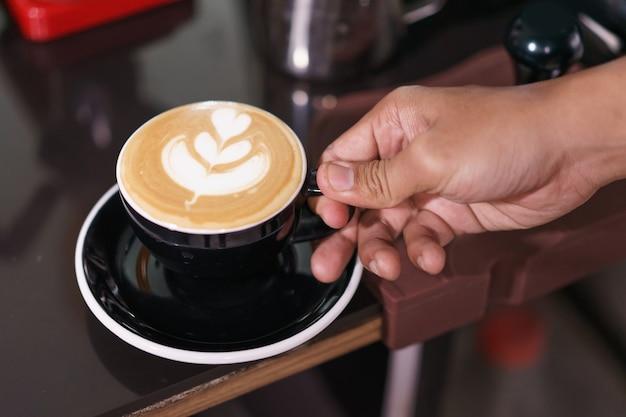 Neem met één hand een koffieschotel klaar om te drinken