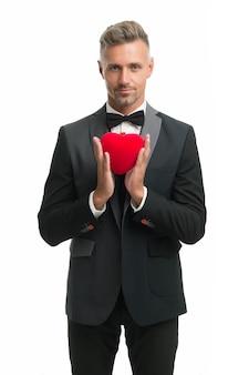 Neem mijn hart. speciale gelegenheid vieren. knappe zelfverzekerde man geïsoleerd op wit. zakenman formele outfit. liefdessymbool op valentijnsdag. smoking man rood valentines hart. klaar voor een romantische date.