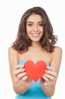 Neem mijn liefde! aantrekkelijke jonge vrouw die een rood papieren hart vasthoudt en naar de camera glimlacht terwijl ze op een witte achtergrond staat