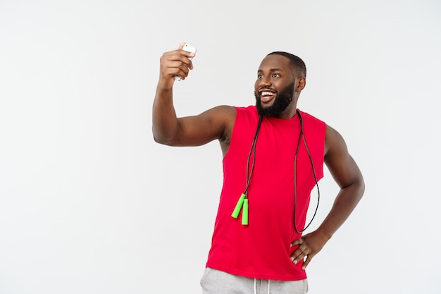 Neemt de portret gelukkige jonge afrikaanse mens stellen geïsoleerd over grijs telefonisch een selfie met kabel en sportslijtage.