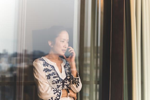 Neergeschoten door raam van vrouw praten op mobiele telefoon in hotelkamer.