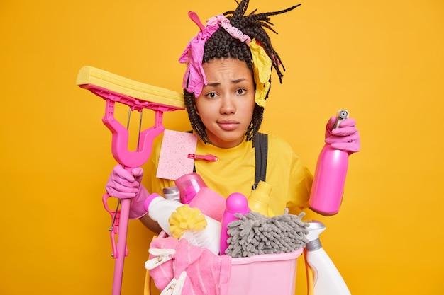 Neergeslagen ongelukkige huishoudster heeft vlechten bezig met het schoonmaken van het huis Premium Foto