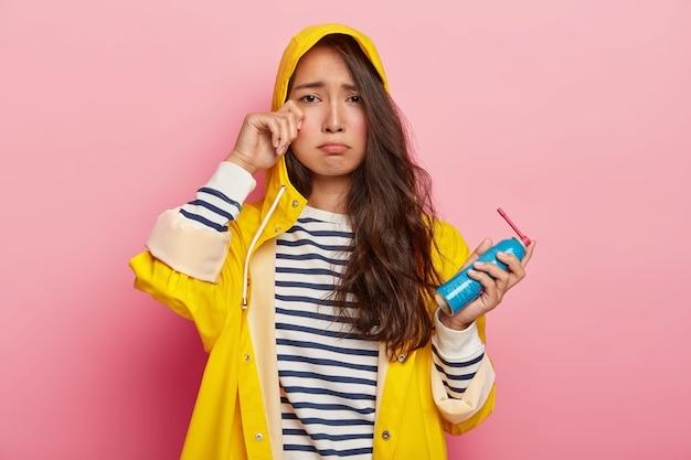 Neerslachtige aziatische vrouw huilt van wanhoop, wrijft in haar oog houdt fles spray vast, draagt gele regenjas