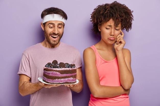 Neerslachtige, boze vrouw verandert van echtgenoot die smakelijke cake op bord houdt, heeft een droevige uitdrukking omdat ze geen zoete desserts kan eten om fit te blijven en slank leidt een gezonde levensstijl, weigert junkfood te eten
