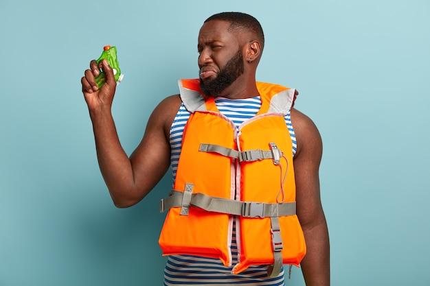 Neerslachtige droevige donkere huid ongeschoren man verloor vechtspel, houdt waterpistool vast, heeft strijd in de buurt van zee, draagt reddingsvest