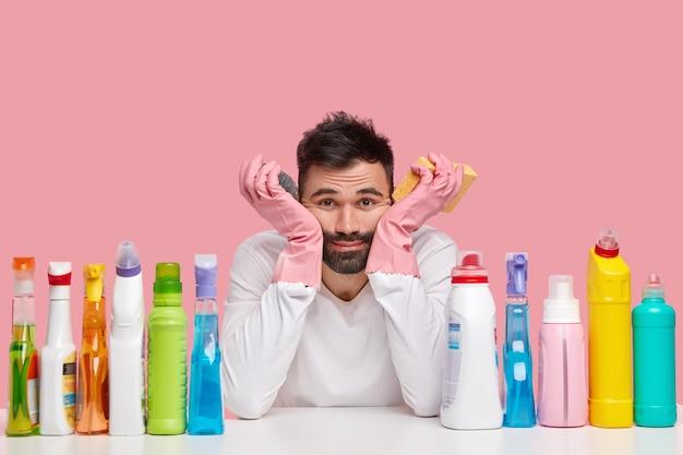Neerslachtige knappe man van schoonmaakdienst houdt beide handen onder de kin, heeft een vermoeide blik, heeft flessen met wasmiddel rond