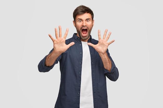 Negatieve emoties concept. stressvolle gekke ongeschoren jongeman gebaart boos, toont handpalmen
