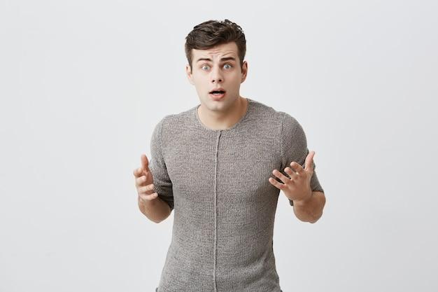 Negatieve emoties en lichaamstaal concept. ontevreden verward knappe blanke man opent mond, kijkt geschokt, ontevreden met resultaten van sportcompetitie.