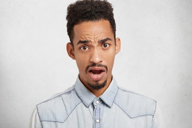 Negatieve emoties en lichaamstaalconcept. ontevreden zwarte man fronst gezicht en kijkt met geopende mond