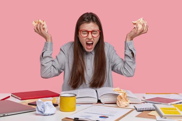 Negatieve emoties, papierwerk en studieconcept. woedende mooie dame fronst haar wenkbrauwen, roept luid