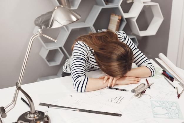 Negatieve emoties. portret van jonge modieuze vrouwelijke freelance architect liggend op handen aan tafel, moe na teveel werken, dromen van slaap