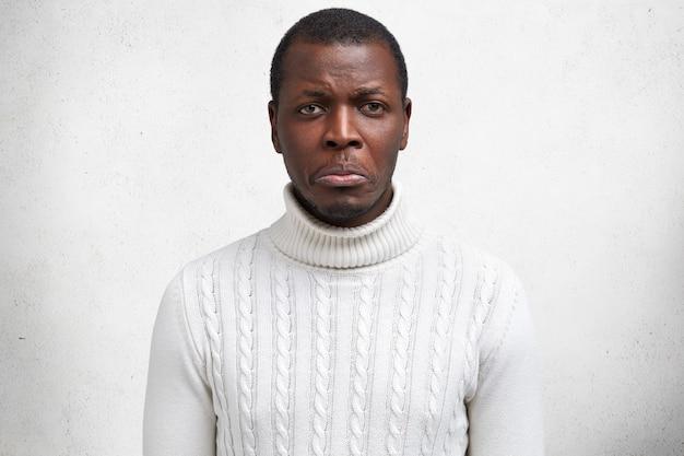 Negatieve gevoelens concept. bedroefd huilen donkere huid afro-amerikaanse man heeft problemen op het werk, wordt ontslagen, voelt wanhoop, geïsoleerd over wit