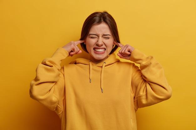 Negatieve gevoelens concept. geïrriteerde vrouw stopt oren en klemt tanden, klaagt over lawaai, negeert onaangename gesprekken, draagt casual hoodie