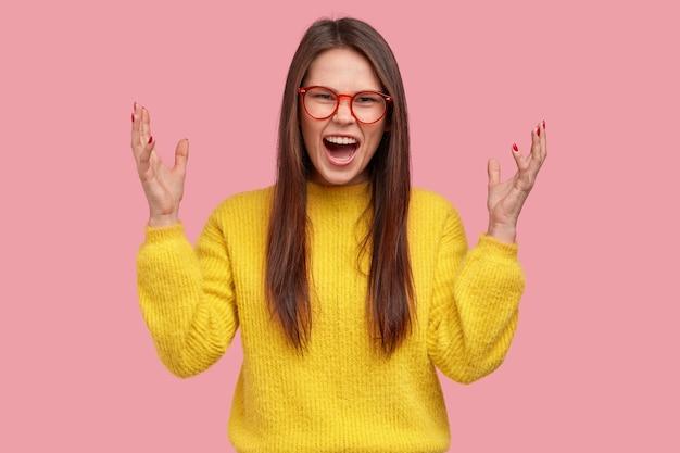Negatieve menselijke emoties concept. emotionele ontevreden gemengd ras vrouw werpt handen met geïrriteerde blik, draagt casual gele kleding