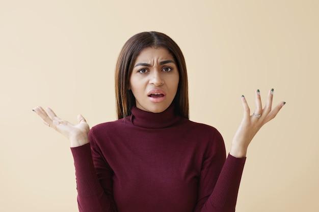 Negatieve menselijke emoties, gevoelens, reactie en houding. emotioneel boos beklemtoonde jonge donkere vrouw fronst en verontwaardigd gebaar maakt, boos op haar vriendje