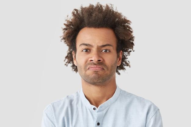 Negatieve menselijke gezichtsuitdrukkingen concept. de gekrulde man tuit zijn lippen, heeft een boze blik en is ontevreden