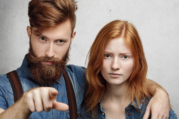 Negatieve menselijke gezichtsuitdrukkingen en emoties. boze blanke man met wazige baard knuffelen zijn verlegen en boos vriendin, wijzend met zijn wijsvinger als teken van verwijt.