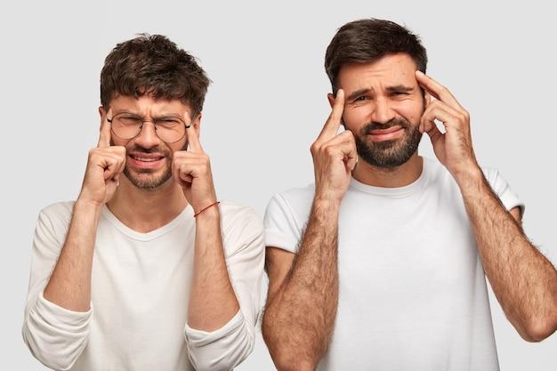 Negatieve menselijke gezichtsuitdrukkingen en emoties. ontevreden mannen houden hun vingers op de slapen, fronsen hun wenkbrauwen in ontevredenheid, hebben hoofdpijn, dragen vrijetijdskleding