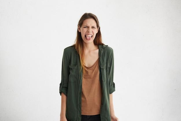Negatieve menselijke reactie, gevoelens en houding. portret van walgt preuts vrouw in vrijetijdskleding grimassen, haar tong uitsteekt, misselijk voelen door slechte geur of stank