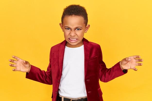 Negatieve reacties en emoties. woedende woedende kleine afro-amerikaanse jongen die zijn tanden op elkaar klemt en zijn hand vasthoudt alsof hij iets knijpt
