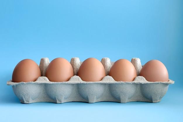 Negen bruine eieren in een papierlade op de lichtblauwe tafel