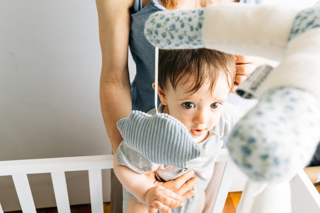 Negen maanden oude baby speelt in de wieg met zijn moeder. haar concept baby en moeder. moederschap