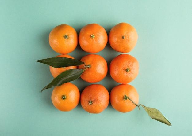 Negen mandarijn- of mandarijnclementine met bladeren op een turquoise papieren achtergrond