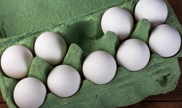 Negen witte kippeneieren in een groene container op een bruin houten tafel, bovenaanzicht.