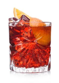 Negroni cocktail in kristalglas met ijsblokjes en stukjes sinaasappel op witte achtergrond