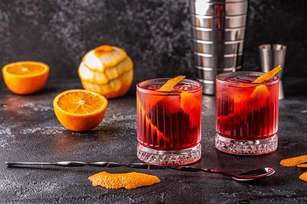 Negroni cocktail met sinaasappelschil en ijs, selectieve aandacht.