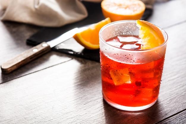 Negronicocktail met stuk van sinaasappel in glas op houten lijst. copyspace