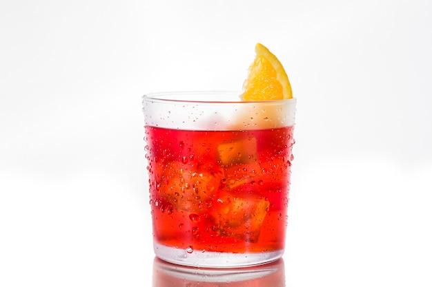 Negronicocktail met stuk van sinaasappel in glas op wit wordt geïsoleerd dat