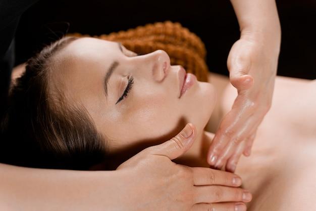 Nek- en gezichtsmassage in de spa. schoonheidsbehandelingen voor een aantrekkelijk vrouwelijk model. ontspanning,