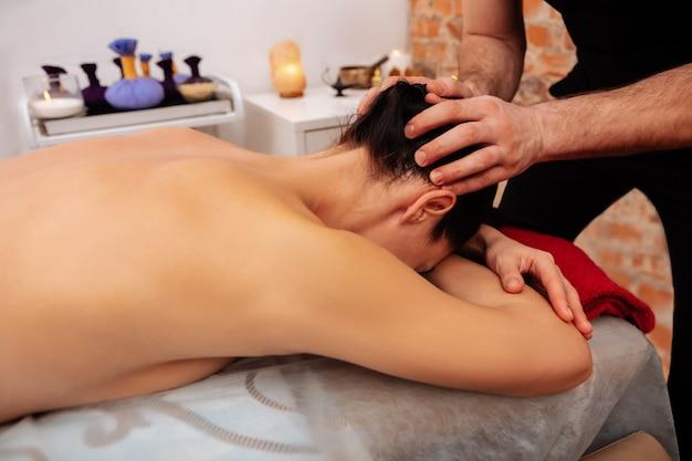 Nek en nek. attente deskundige meester masseert zachtjes het hoofd van een langharige vrouw als afwerkingszone